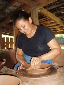 Plates and bowls are a popular export. Here, a sculptor smoothes the clay on a pottery wheel -the first step of many.