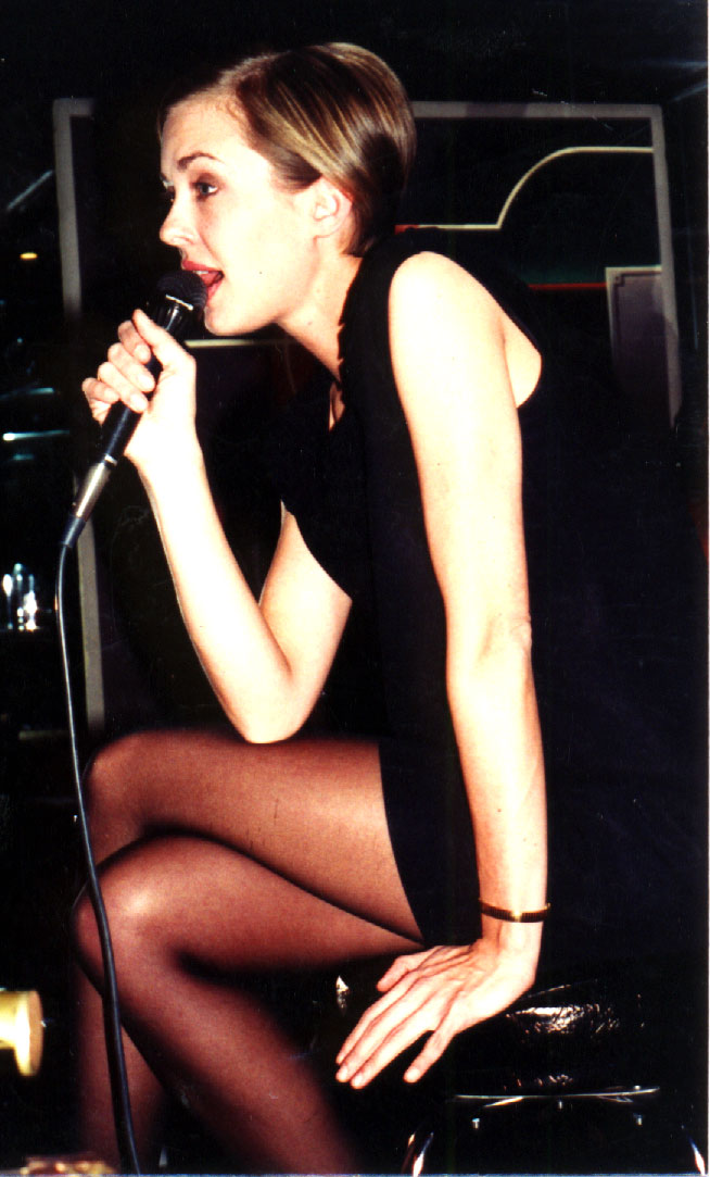 Stephanie sits on a stool and sings into a mic. She's wearing a watch and has a very short haircut.