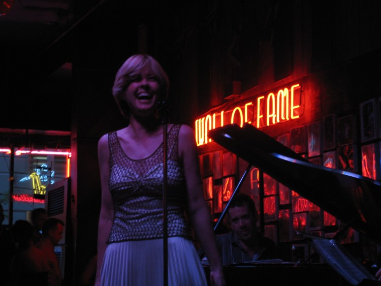 Stephanie smiles and laughs on stage in front of the neon WALL OF FAME sign at Andys - pure joy