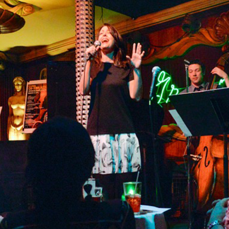 Stephanie sings passionately on stage with her band behind her and a gold naked lady statue at the Green Mill Chicago - fabulous!