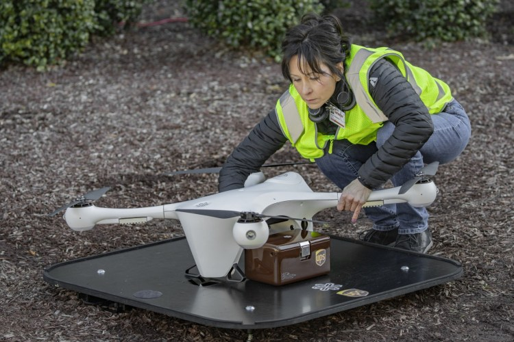 UPS worker tightening a package onto a delivery drone as a sample test launch.