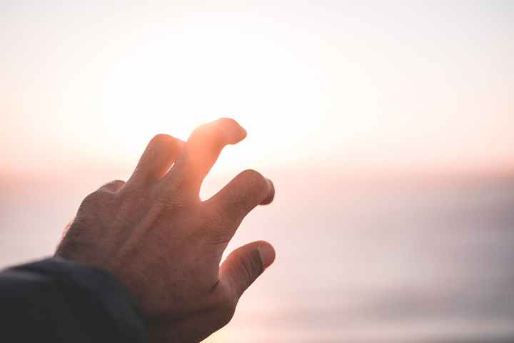 man covering bright sunlight shining on sunset sky