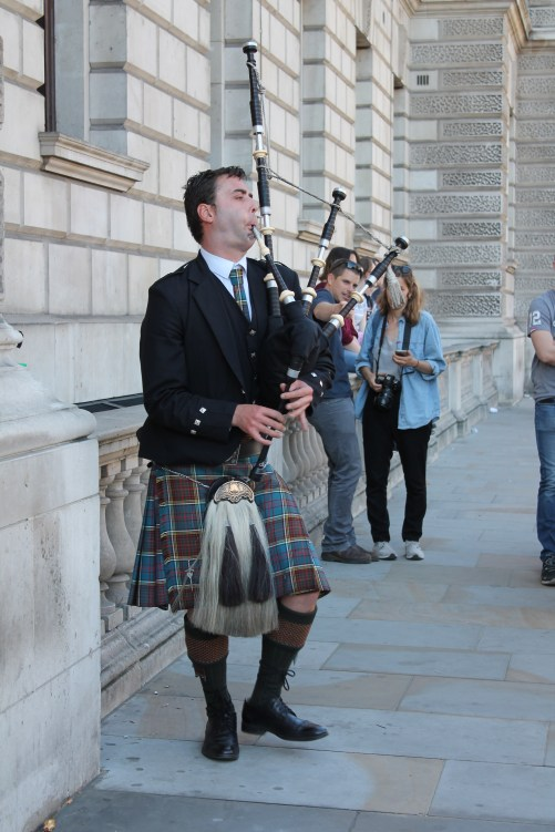 The familiar sounds of Scottish bagpipes are played by a man wearing a traditional kilt.