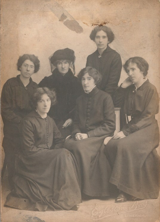 black-and-white group portrait of Catherine Daly and five of her daughters, in black formal attire, seated