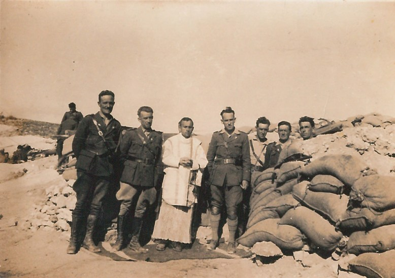 black-and-white picture of a group of eight men posing at entrance to the trenches, Padre Alonso in white vestments