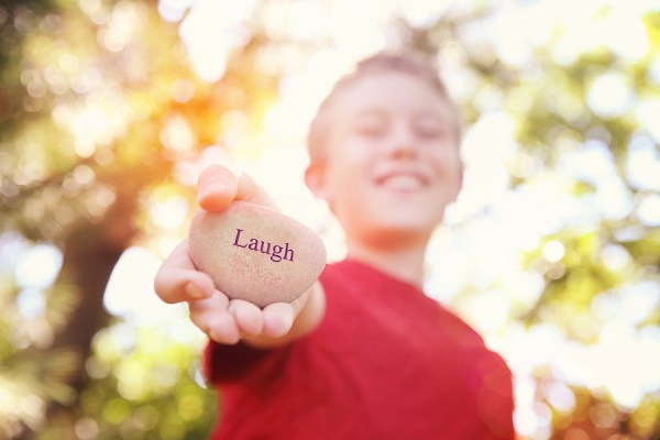 Boy laughing and holding a stone with the word Laugh. Instagram  effect