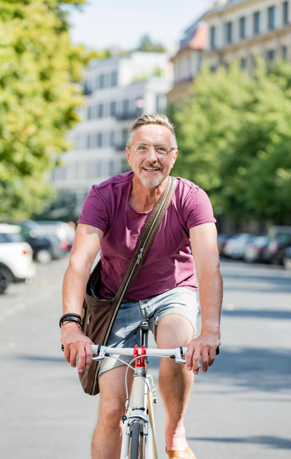 Active senior man in his early 60s enjoys city life in summer.