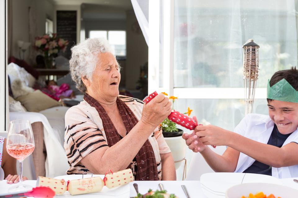 Grandma and grandson pull Christmas cracker at table