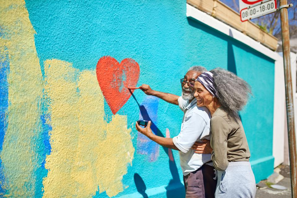 Happy senior couple painting heart-shape mural on sunny wall