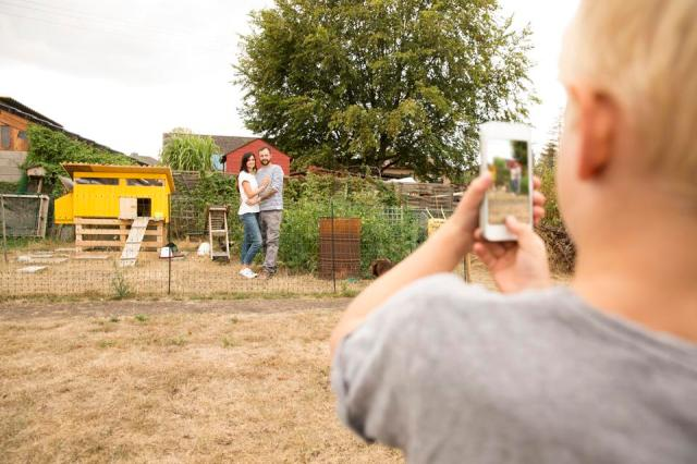 Boy taking cell phone picture of parents standing at chickenhouse in garden
