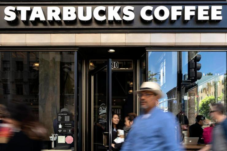 Pedestrians walk by the Hollywood Starbucks Coffee shop in...