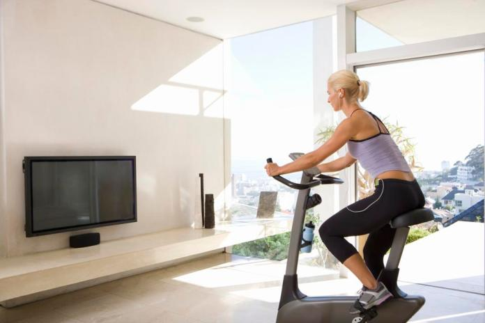 Mature woman on exercise bike watching television at home