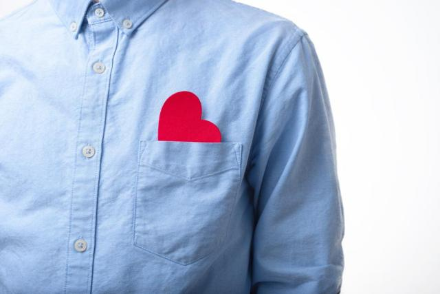 Heart shape in a pocket of a blue shirt. Love, alone, single, in love concept.