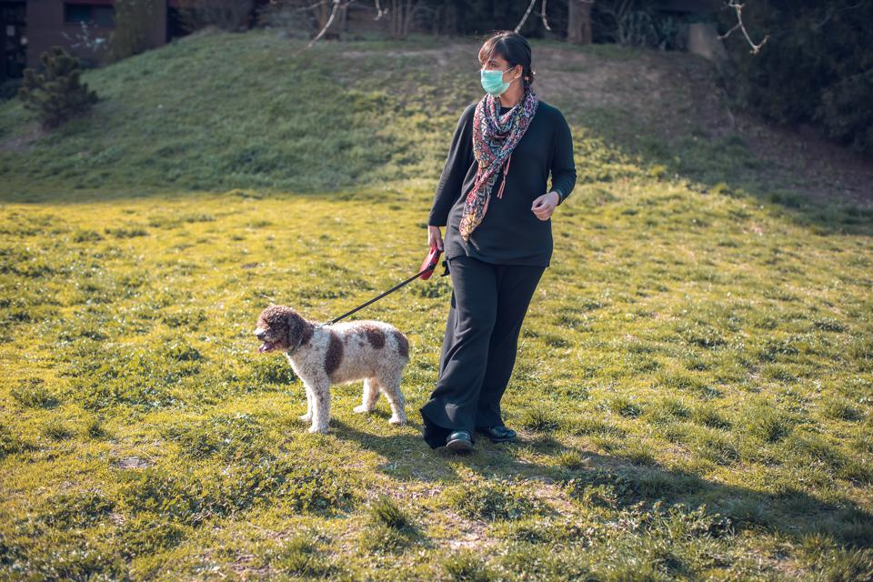 woman walking dog in the park with face mask