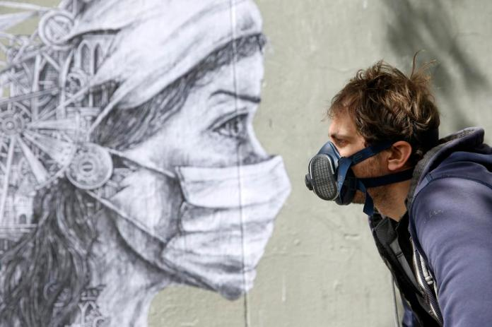 French street artist Ardif in front of his work to pay tribute to medical workers on May 12, 2020 in Paris, France.