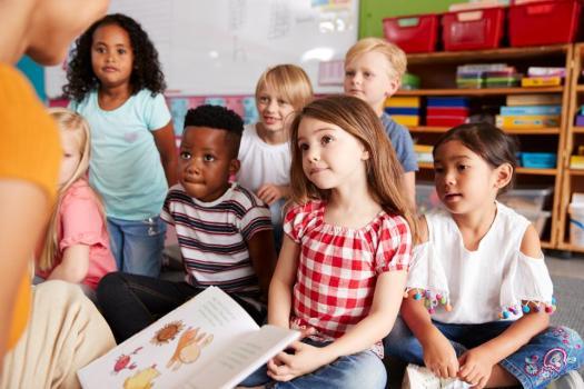 Groupe d'élèves de l'école élémentaire assis sur le sol à l'écoute de l'enseignante Lire l'histoire