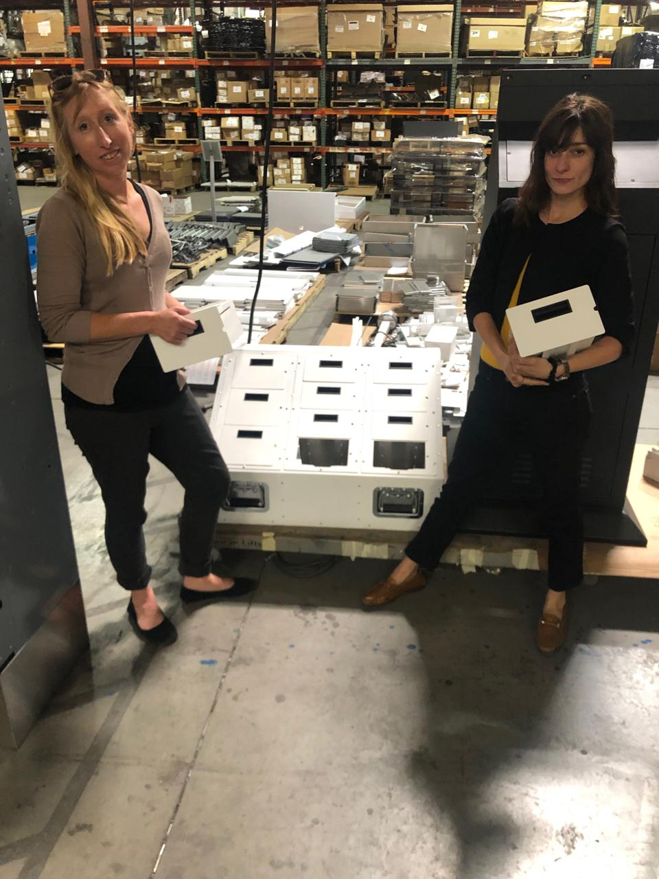 Two women standing in front of the machine they created