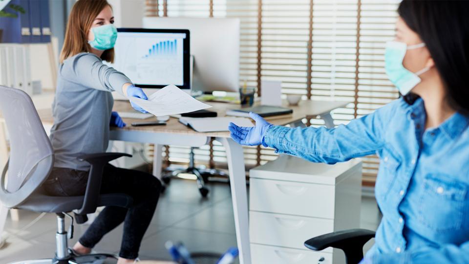 Women at an office wearing face masks.