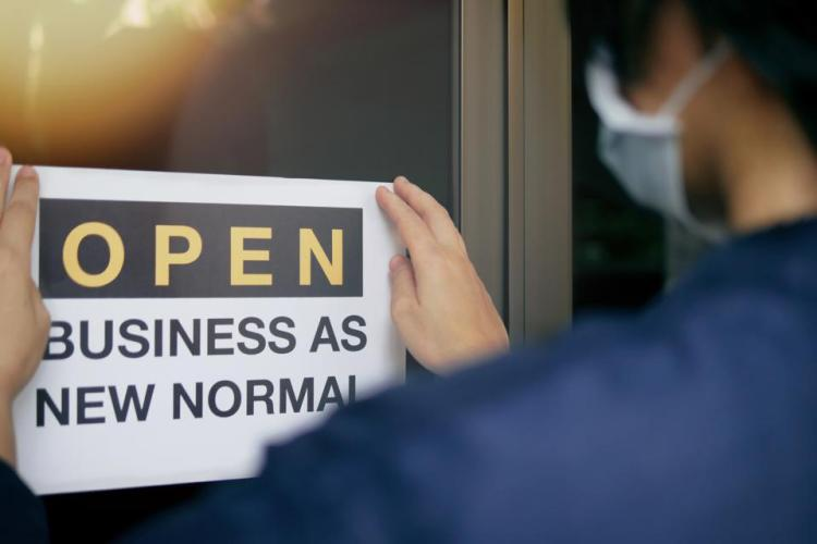 Rear view of business owner wearing medical mask placing open sign ″OPEN BUSINESS AS NEW NORMAL″ on front door.