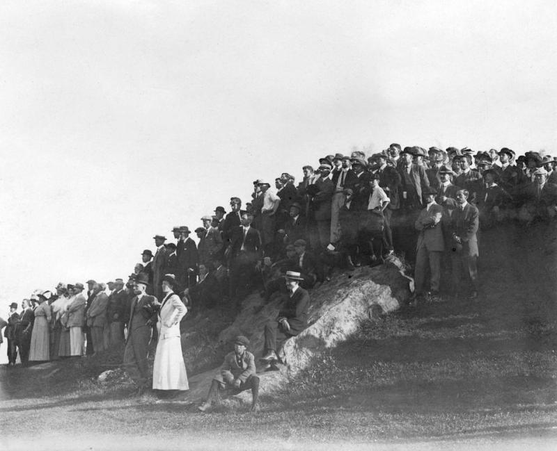a large group of spectators stands on a mound near the fairway to watch the 1911 American amateur