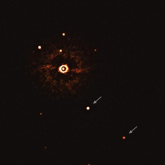 The two planets are visible as two bright dots in the middle (TYC 8998-760-1b) and lower right corner (TYC 8998-760-1c) of the frame, marked by arrows.  Other bright spots are visible in the picture, which are the background stars.  By capturing different images at different times, the team was able to distinguish planets from background stars.