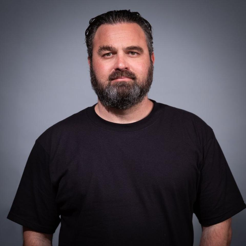 Elliot headshot black t-shirt. beard.