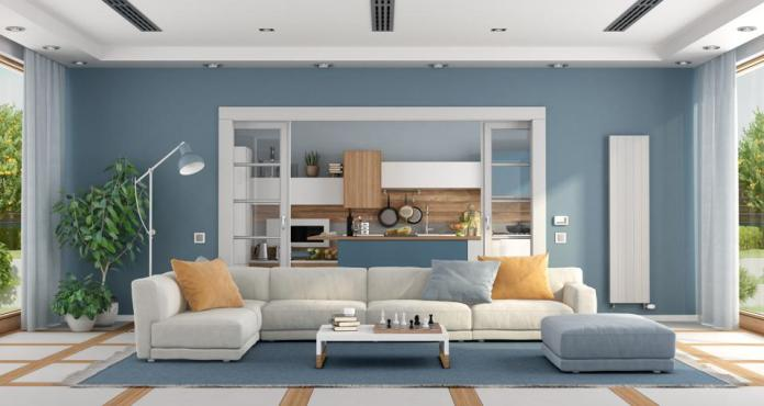 Living room with sofa and modern kitchen on background