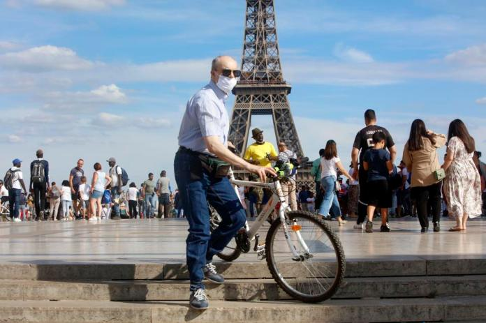 Tourists wearing protective masks walk in front of the Eiffel Tower in France. August 2, 2020.