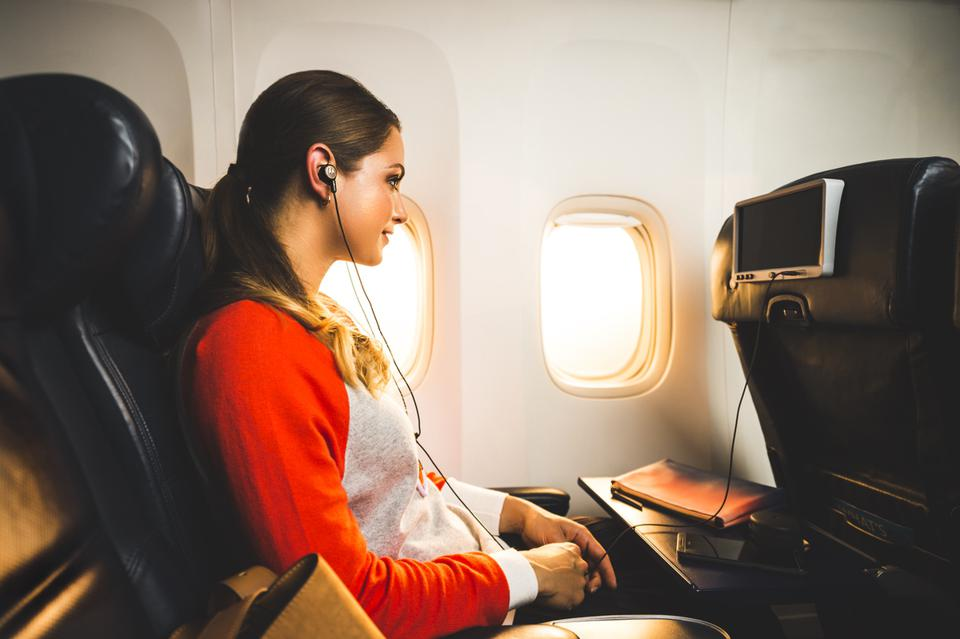 Woman in aircraft watching a movie and listening to Motorola Tech3 earphones