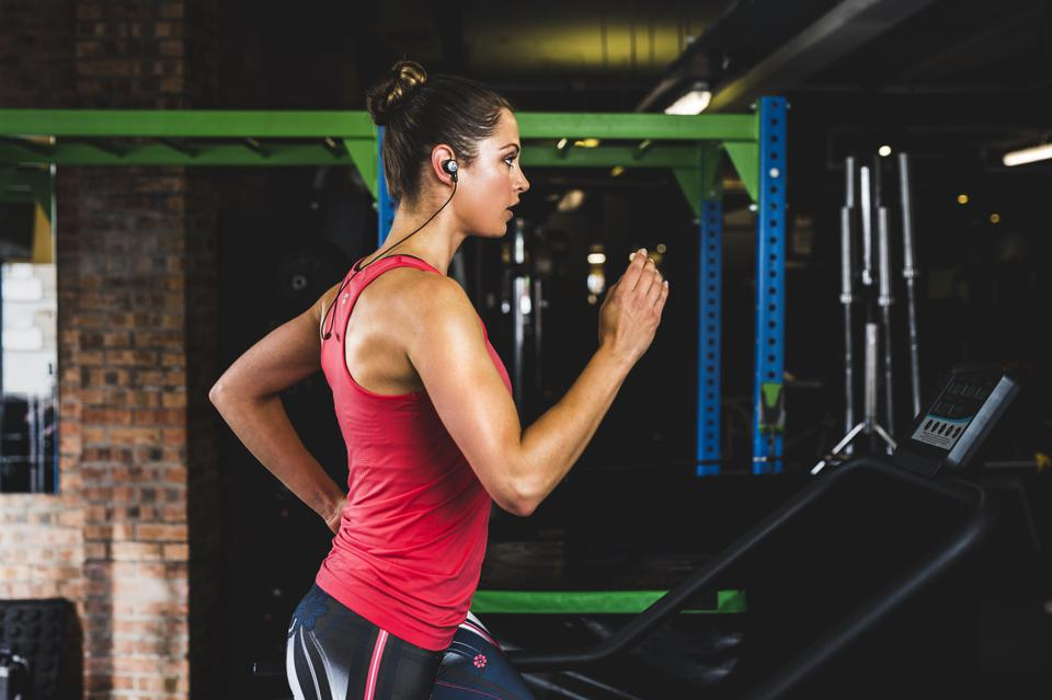 Woman running in a gym wearing a red vest and listening to Motorola Tech3 earbuds in sport loop configuration