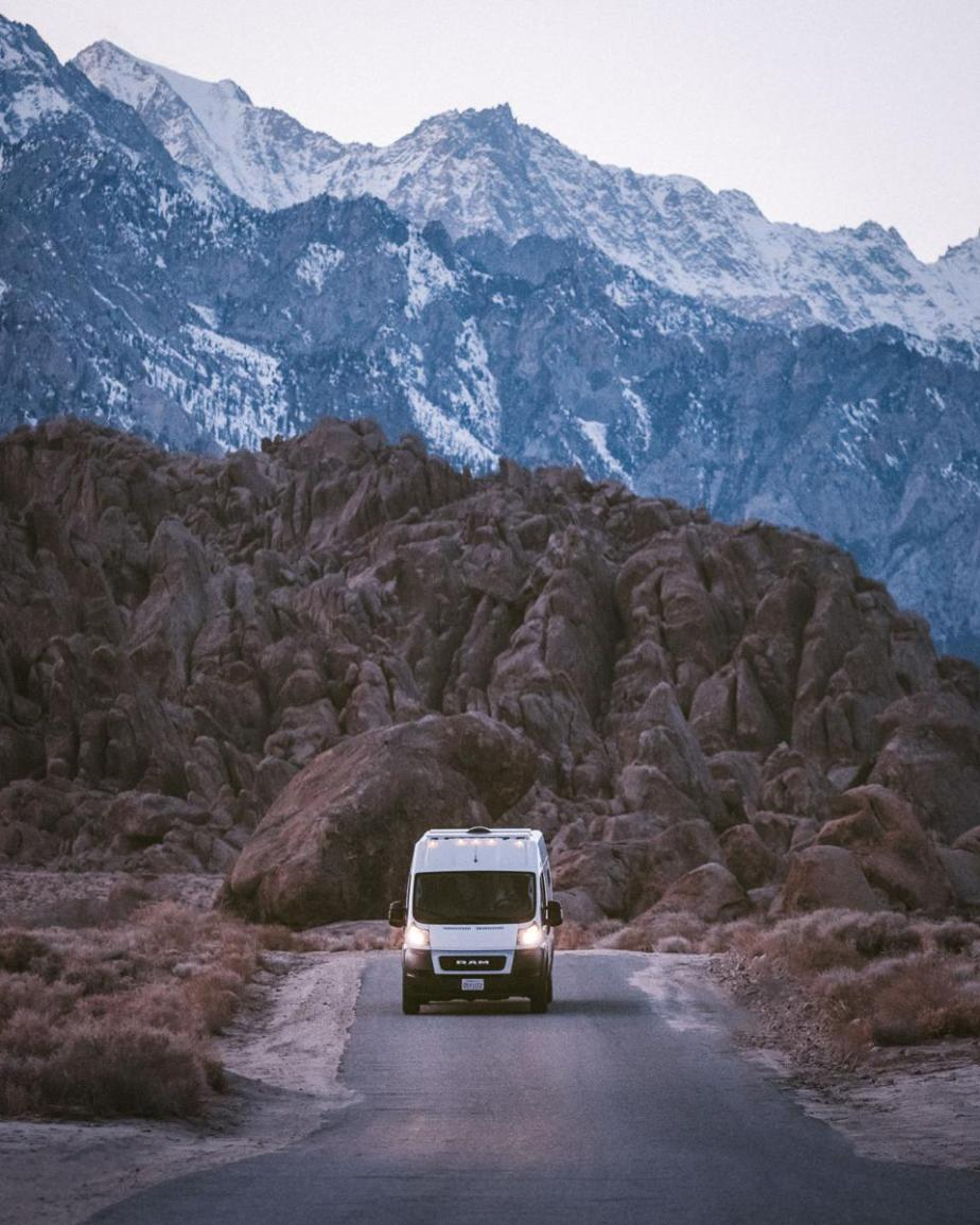 A white van driving towards the viewer beneath craggy mountain peaks at dusk.