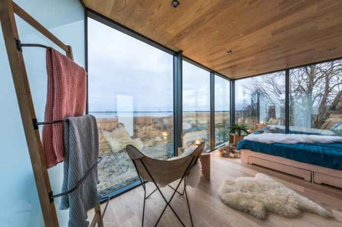 Sumptuous interiors inside a cabin with glass doors overlooking the land.