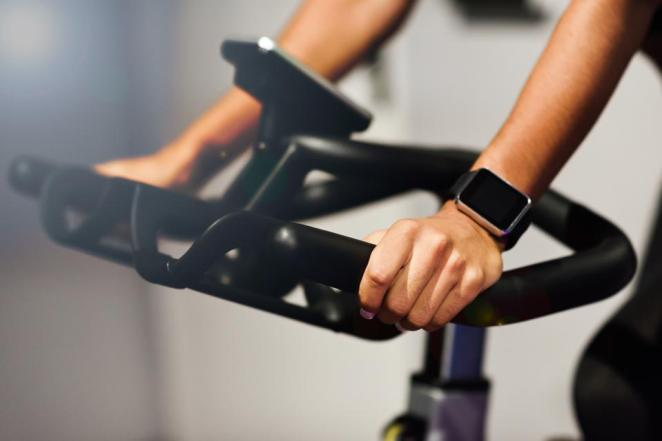 Woman at a gym doing exercising or cyclo indoor with smart watch