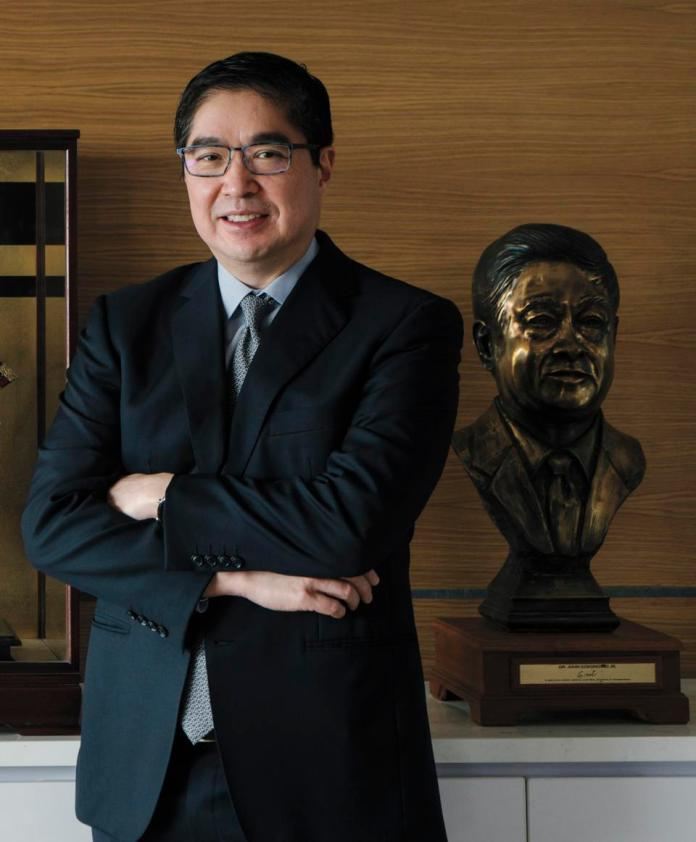 Lance Gokongwei in his office, next to a bronze bust sculpture of his father.