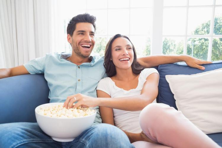 Attractive couple watching tv on the sofa
