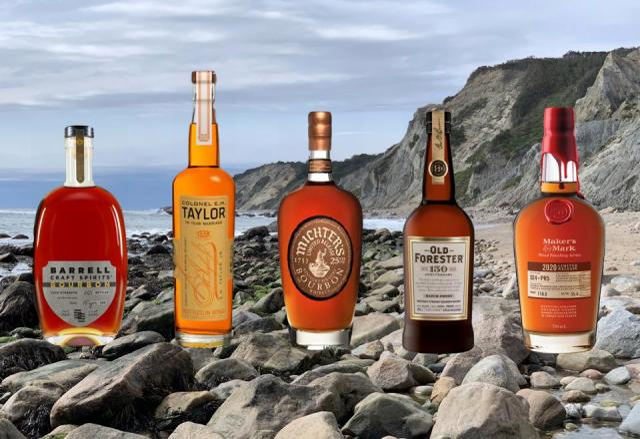 Five bottles of exceptional bourbon sit on a beach in Block Island, Rhode Island