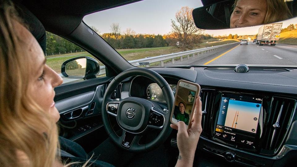 A distracted driver viewing a cell phone while driving.