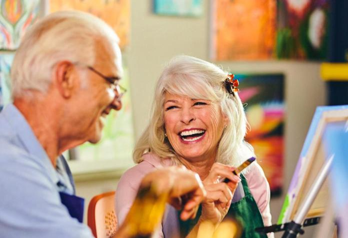 Two older adults in an art class at Revel Communities properties.