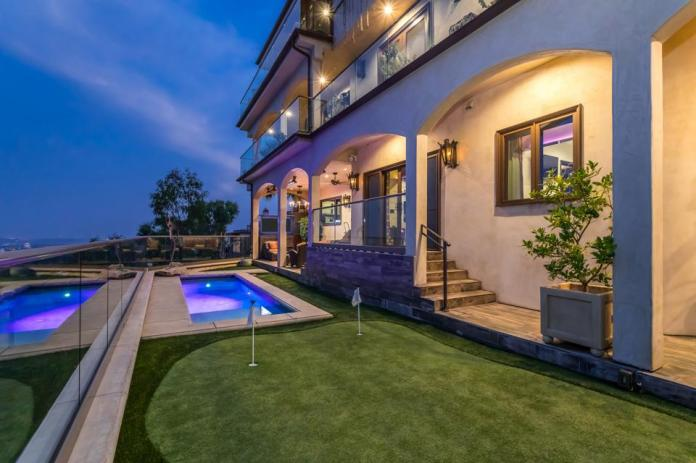 A putting green and plunge pool sit on the foreground of comedian Ron White's Beverly Hills-area home.