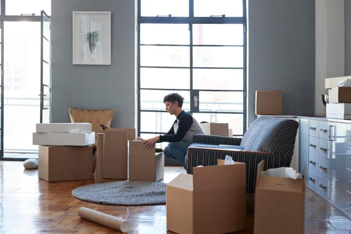 Woman wrapping boxes in stylish apartment