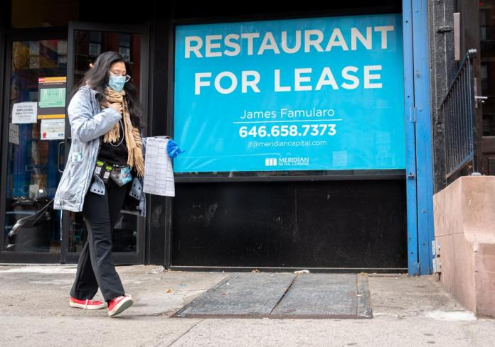 A person walks by a sign that reads, ″restaurant for lease″ outside a restaurant in Hell's Kitchen (Photo by Noam Galai/Getty Images)