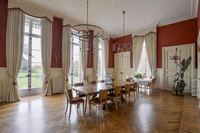 The dining room features white paneling, floor-to-ceiling windows and chandeliers.