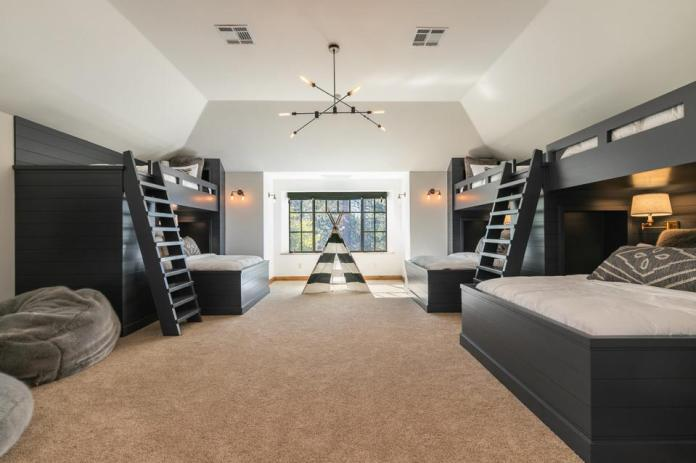 A bunk room features six custom beds crafted in dark wood with carpet