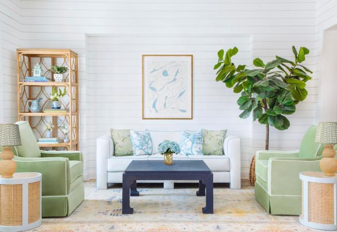 A living room with green and white sofas, a grasscloth coffee table, rattan side tables and bookcase.