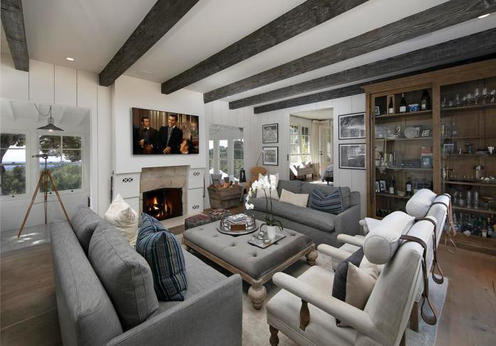 A living room with warm woods and cool tones and a fireplace, shelves and a seating area.