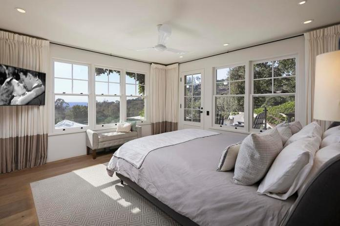 A master bedroom features windows and a ocean view.