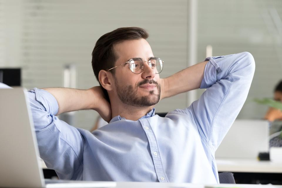 Relaxed businessman taking break holding hands behind head enjoying rest