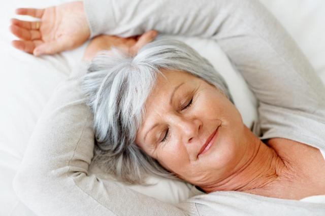 Closeup of an elderly woman fast asleep in bed.