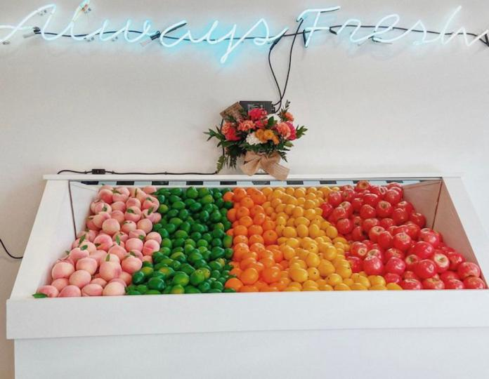 Produce and a neon sign that reads ″Always Fresh″