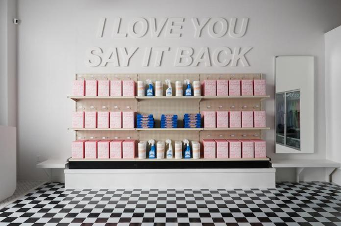 Shelves of products and a statement installation reading ″I love you. Say it back.″